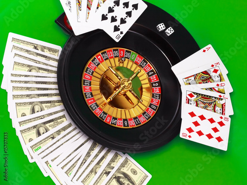 The casino roulette and playing cards on green broadcloth.