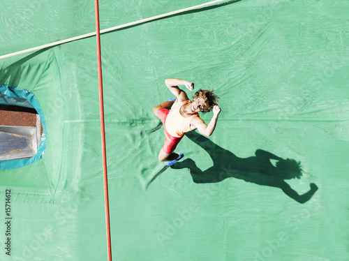 Athlete cheering as he hits the mat after a pole vault