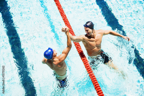 Two swimmers in a pool joining hands
