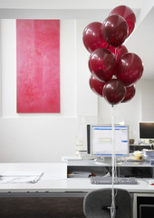 Empty desk with red balloons tied to chair