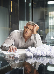 Businessman sitting with crumpled papers in an office