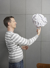 Man in office balancing large ball of paper on finger