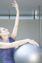 Woman stretching holding a pilates ball