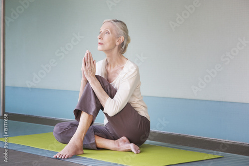 Woman sitting on a yoga mat with hands praying