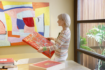 Woman holding a painting in a modern home