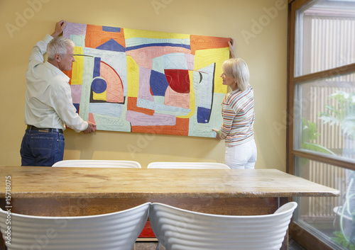 Couple hanging artwork in modern home