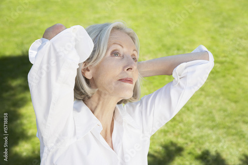 Woman relaxing outdoors with hands behind head
