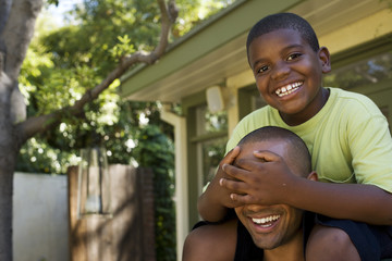 Man piggybacking young boy covering eyes in back yard