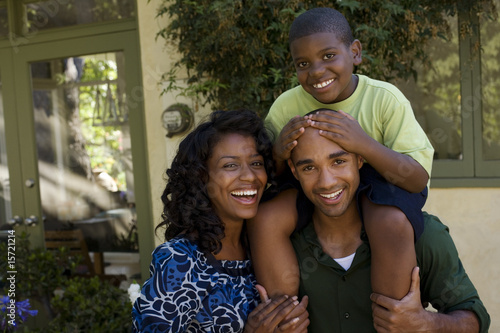 Man piggybacking young boy and standing beside woman