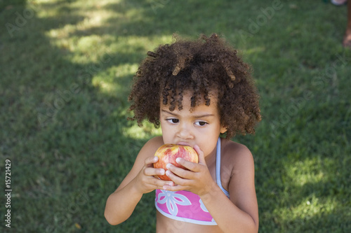 Girl in swimwear eating apple in yard