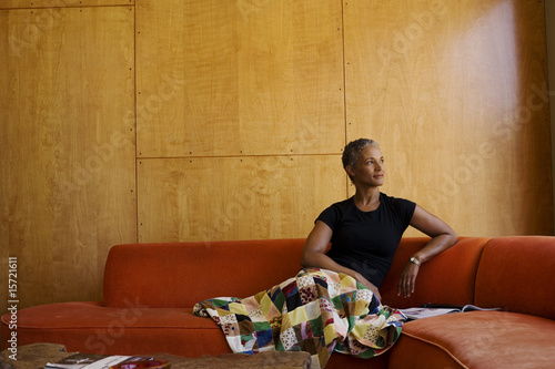 Woman sitting on sofa in modern home