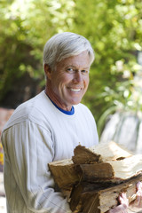 Man carrying firewood smiling