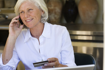 Woman using credit card to shop over the phone