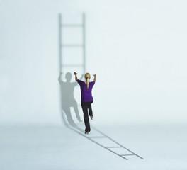 Woman climbing a ladder's shadow