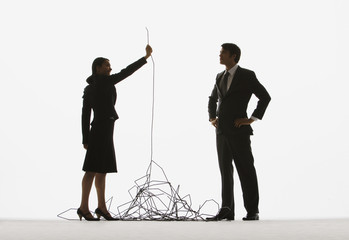 Two businesspeople by a pile of cable with the woman holding one end