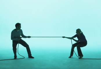 Man and woman playing tug of war