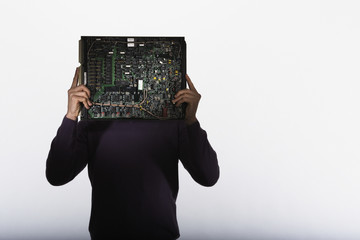 Man standing with computer motherboard in front of face