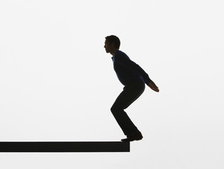 Man about to jump backwards off a plank