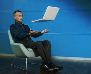 Man sitting with laptop floating over his lap