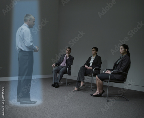 Three businesspeople watching a hologram of a businessman