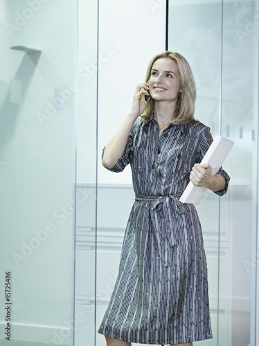 Businesswoman on her mobile phone in office hallway