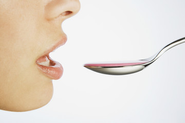 Woman taking a spoonful of medicine