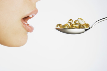 Woman taking a spoonful of pills