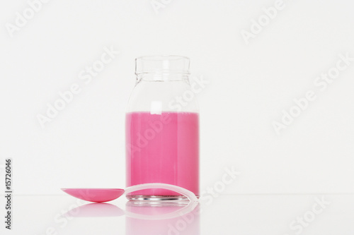 A container of medicine with a spoonful in front of it