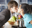 Couple kissing in kitchen over counter