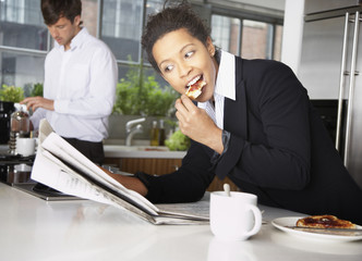 Woman eating toast with man in background