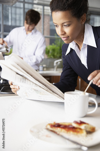 Woman with toast and man in background pouring coffee