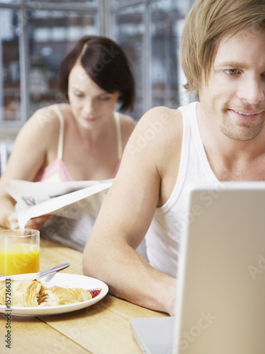 Couple in a kitchen with the woman reading and the man on a laptop