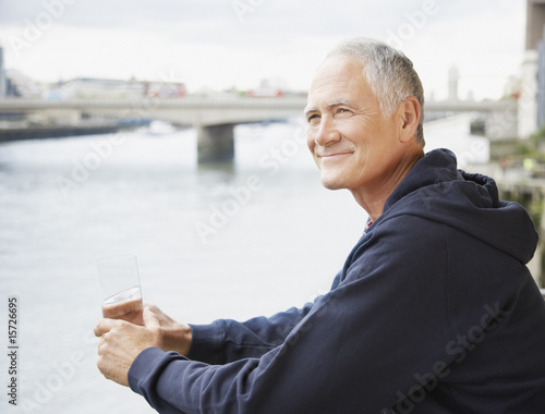 Man with glass of water leaning by river