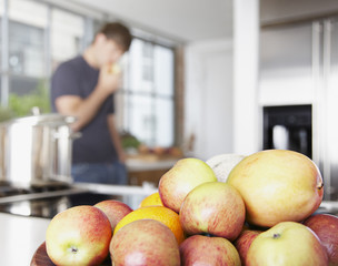 Bowl of mangos and nectarines with man in background eating