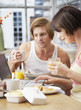 Couple at breakfast with laptop in modern home