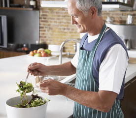 Man preparing a salad in kitchen
