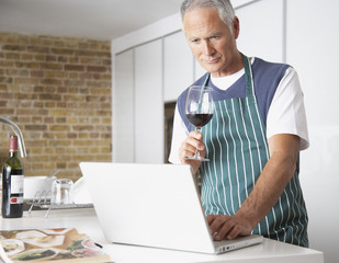 Man looking at laptop with glass of wine