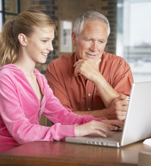 Man and girl looking at laptop