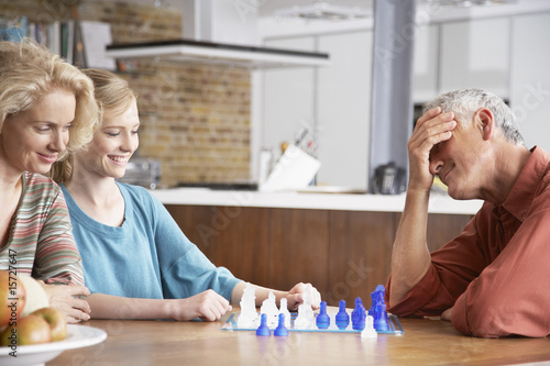 Couple and girl playing chess