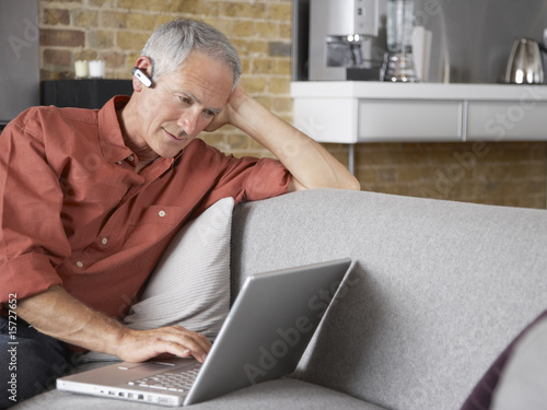 Man wearing headset sitting with laptop