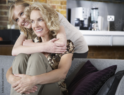 Woman and girl embracing in living room