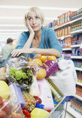 Woman with shopping trolley full of groceries