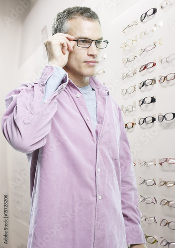 Man trying on glasses in optical shop