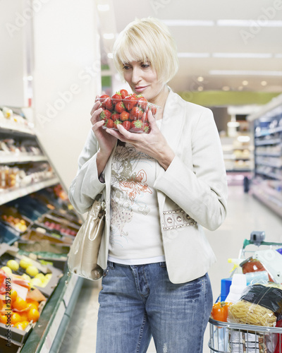 Woman holding strawberries grocery shopping