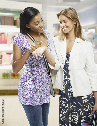 Two women trying on perfume in a store