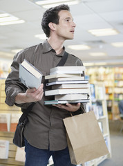 Man with stack of books in store