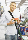 Man eating watermelon at market