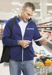 Man looking at bill in grocery store