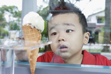Boy looking at ice cream cone through glass