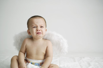 Baby crying wearing wings